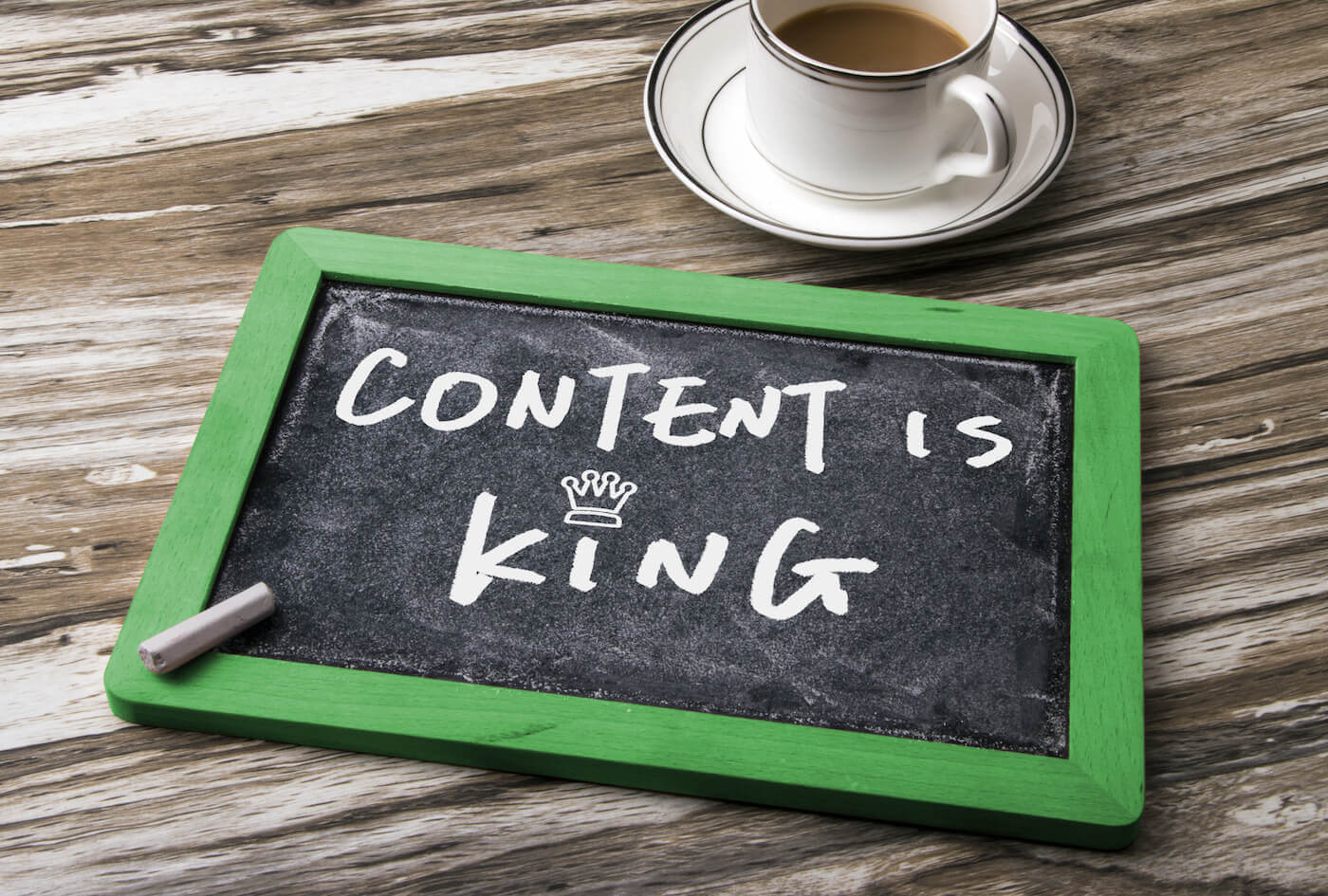 white chalk writing on a blackboard which says content is king