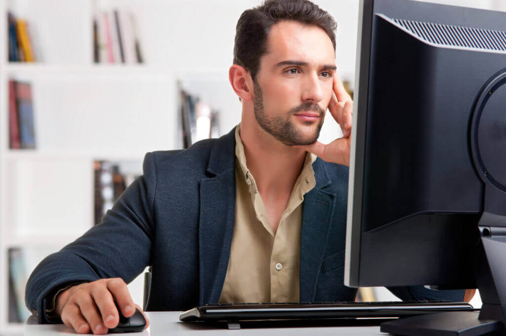 man staring at a computer screen possibly looking online at a hotel