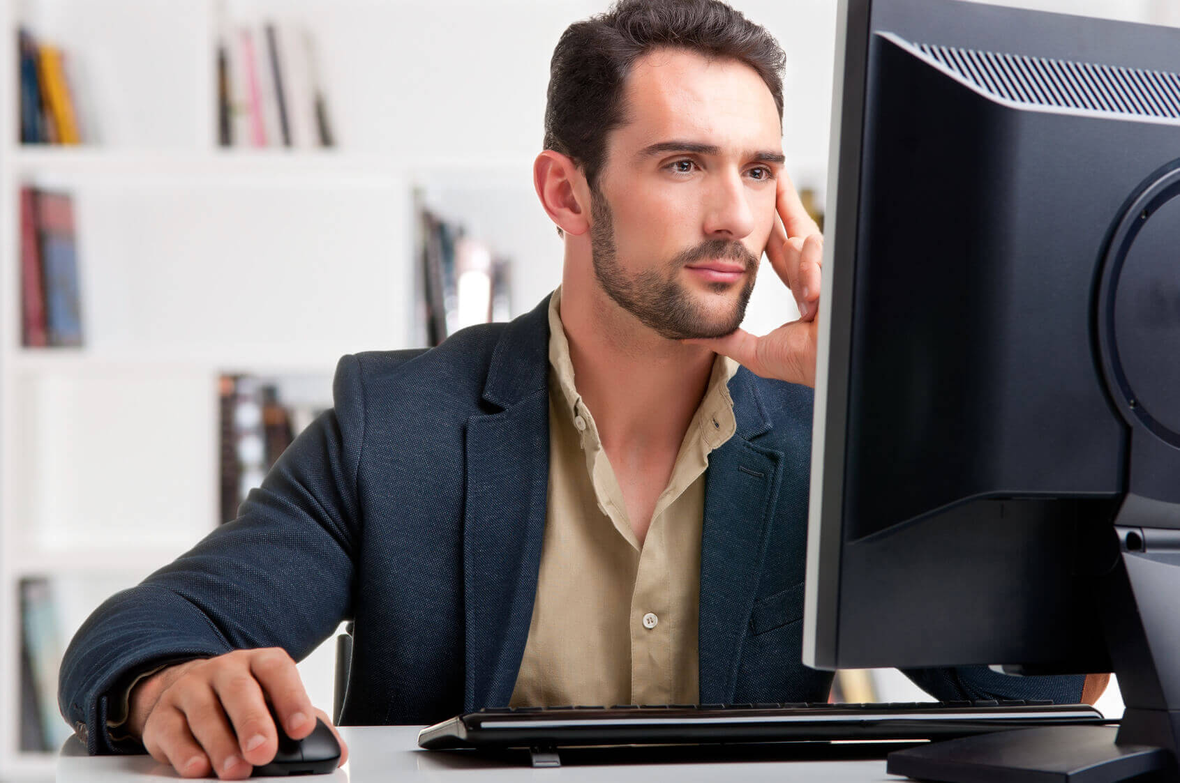 man staring at a computer screen possibly reading an email before booking a hotel
