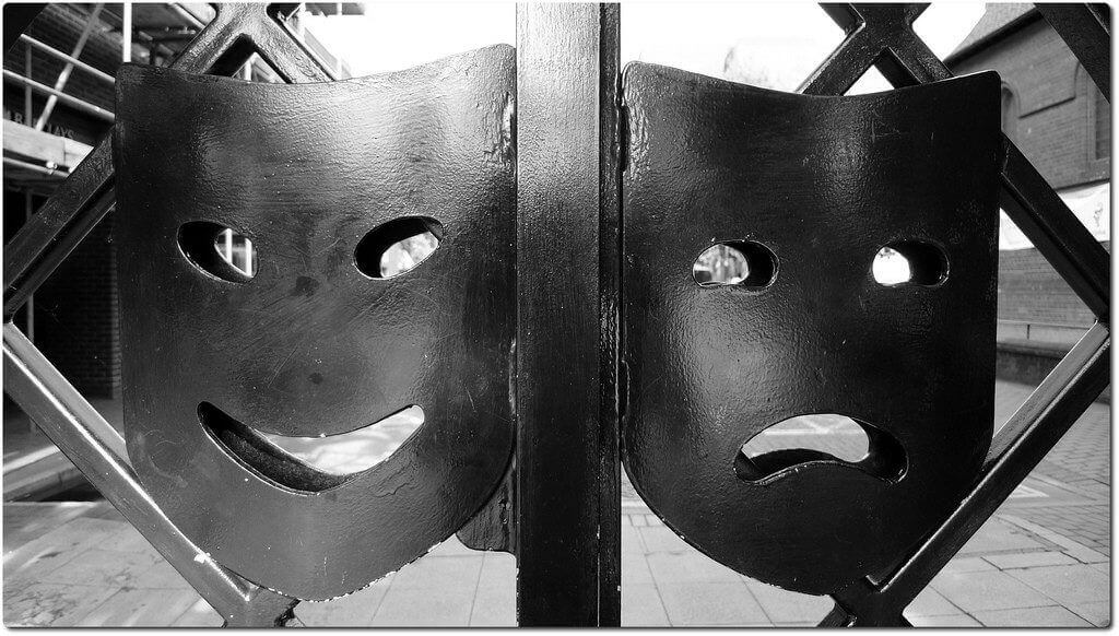 gate with two metal faces one smiling and one frowning illustrating different views amongst hotels about OTAs