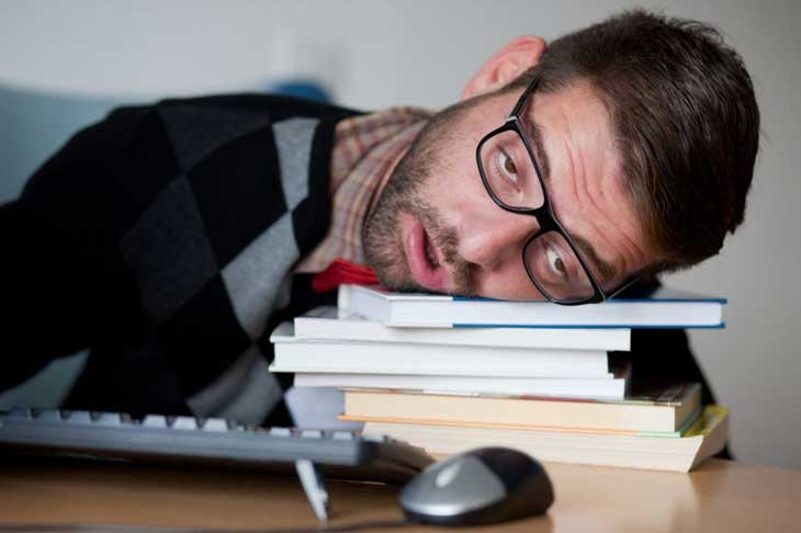 man falling asleep on a pile of books