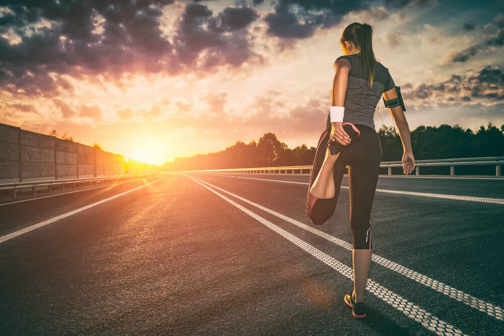 women runner looking towards the sun rising on horizon