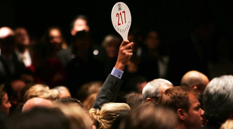 man holding up auction paddle