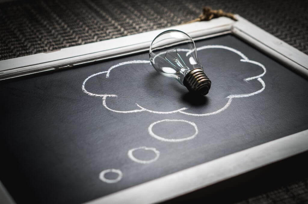 lightbulb on a chalk board with bubble drawing reflecting ideas that come from commercial strategy
