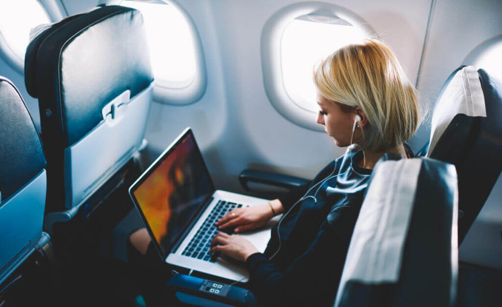 person on laptop during a flight which is much needed revenue for the airlines