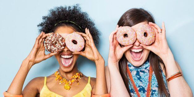 two people having fun looking through donuts reflecting how hotels should view their marketing in a different way