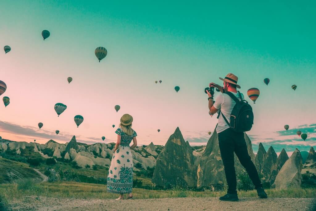 picture of a man taking a photo of a lady looking at air balloons which can then be used in creative advertising