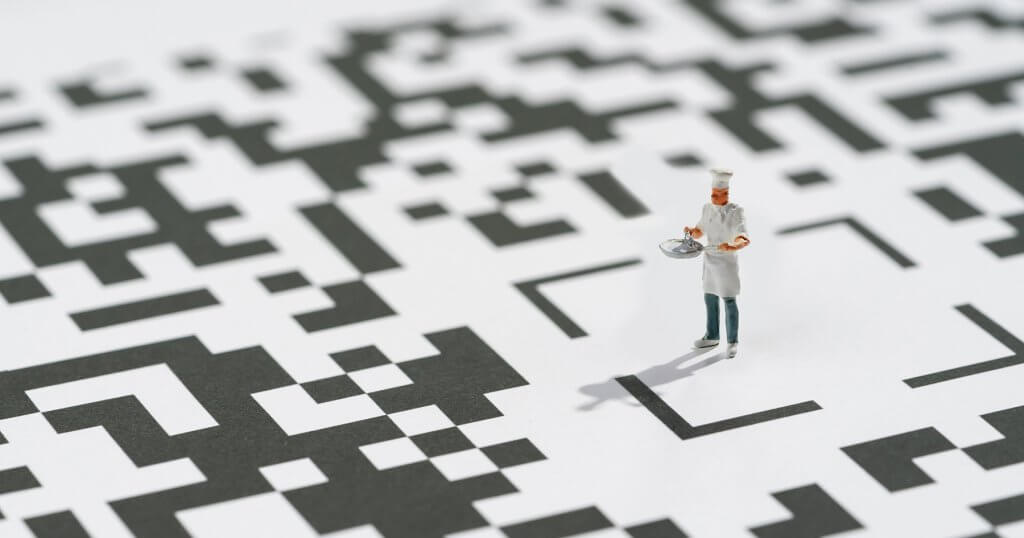 mini figure of a chef standing on a qr code illustrating different ways you can gather guest information to produce data analytics to help your restaurant