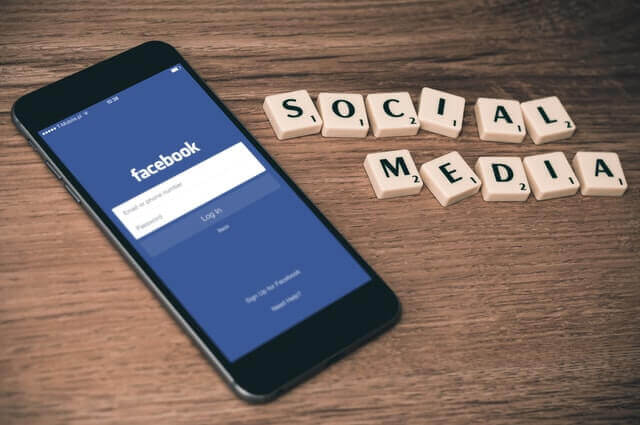 mobile phone with facebook and letters spelling social media depicting importance of hotels social listening
